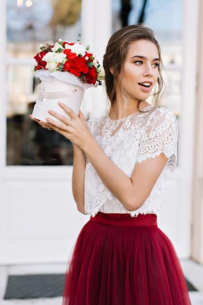 肖像画の通りにマルサラチュールスカートで美しい少女。彼女はバラのブーケを持ち、横を向いている 無料写真