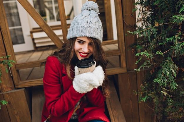 Портрет красивой девушки в красном пальто, вязаной шляпе и белых перчатках, сидя на деревянной лестнице на открытом воздухе. она держит кофе и улыбается в сторону. Бесплатные Фотографии