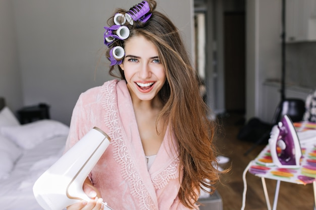 Ritratto bella ragazza in accappatoio rosa con riccioli sulla testa a casa. tiene l'asciugacapelli, sorridendo. Foto Gratuite