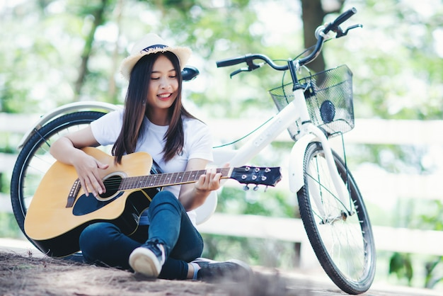 Portrait of beautiful girl playing the guitar with bike at nature Free Photo