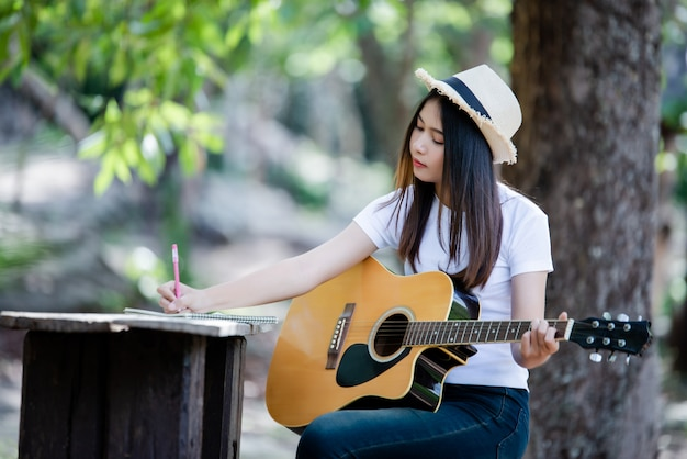 Portrait of beautiful girl playing the guitar with writing at nature Free Photo