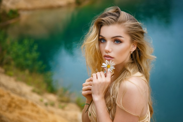 Portrait of a beautiful girl with a daisy in her hands, beautiful make-up Premium Photo