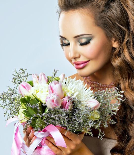 Ritratto di una bella ragazza con fiori in mano. la giovane donna felice tiene il mazzo di fiori Foto Gratuite