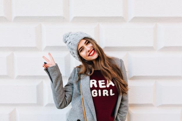 Портрет красивой девушки с длинными волосами и красными губами на серой стене. на ней серое пальто и вязаная шапка. она показывает знак и улыбается. Бесплатные Фотографии