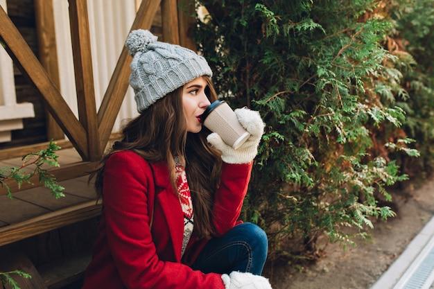 Bella ragazza del ritratto con capelli lunghi in cappotto rosso, cappello lavorato a maglia e guanti bianchi che si siedono sulle scale di legno vicino ai rami verdi all'aperto. beve caffè e guarda a lato. Foto Gratuite