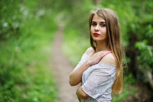 Portrait of beautiful girl with red lips at spring blossom garden, wear on red dress and white blouse. Premium Photo