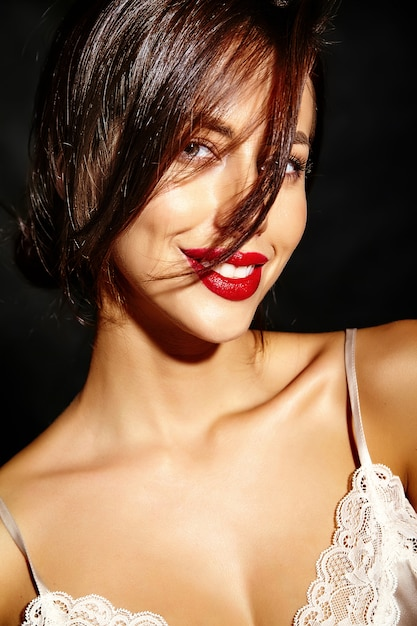 Portrait of beautiful happy cute sexy brunette woman with red lips in pajamas lingerie on black background Free Photo