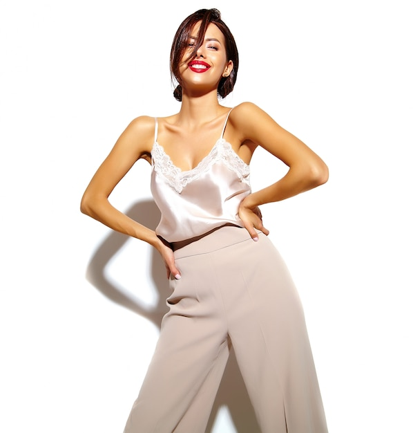 Portrait of beautiful happy cute sexy brunette woman with red lips in wide classic pants on white background Free Photo