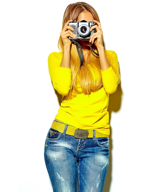 Portrait of beautiful happy cute smiling blond woman girl in casual summer clothes takes photos holding retro photographic camera Free Photo