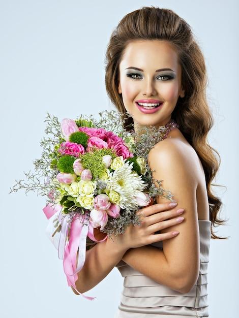 Ritratto di bella ragazza felice con i fiori nelle mani. la giovane donna attraente tiene il mazzo di fiori primaverili Foto Gratuite