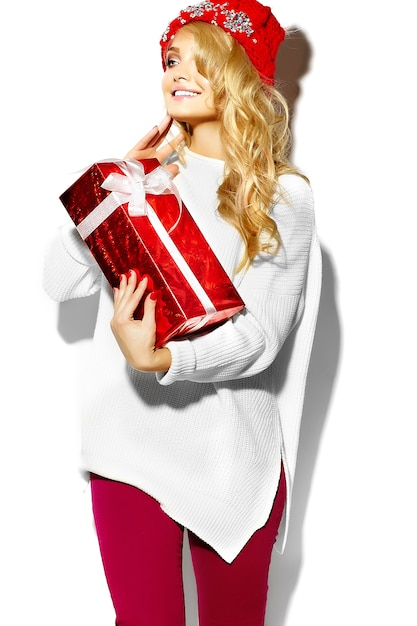 Portrait of beautiful happy sweet smiling blonde woman woman holding in her hands big christmas gift box in casual red hipster winter clothes, in white warm sweater Free Photo