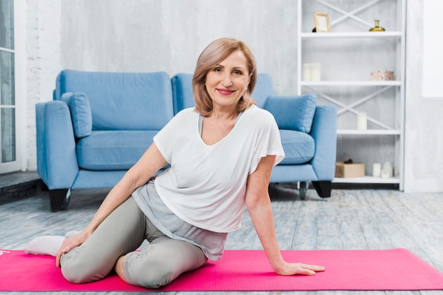 Portrait of a beautiful happy woman sitting on pink yoga mat looking at camera Free Photo
