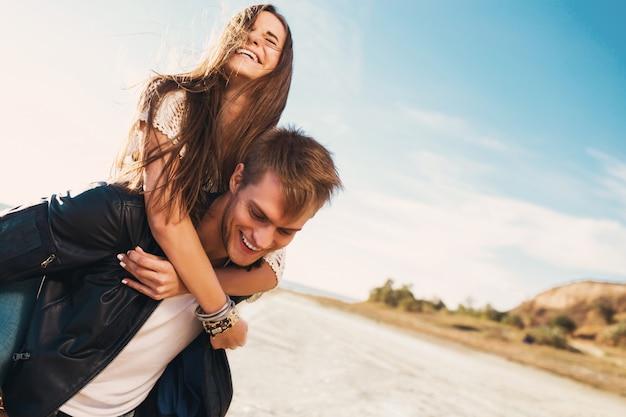 美しい健康な若い大人のガールフレンドとボーイフレンドの幸せを抱いての肖像画。ビーチ沿いの日当たりの良い春に恋に若いきれいなカップル。暖かい色。 無料写真
