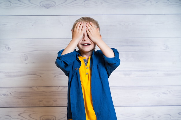 Portrait of a beautiful kid boy in yellow t-shirt and denim jacket, shirt. boy standing on a white wooden background. 5 years old boy. closes eyes with hands. Premium Photo