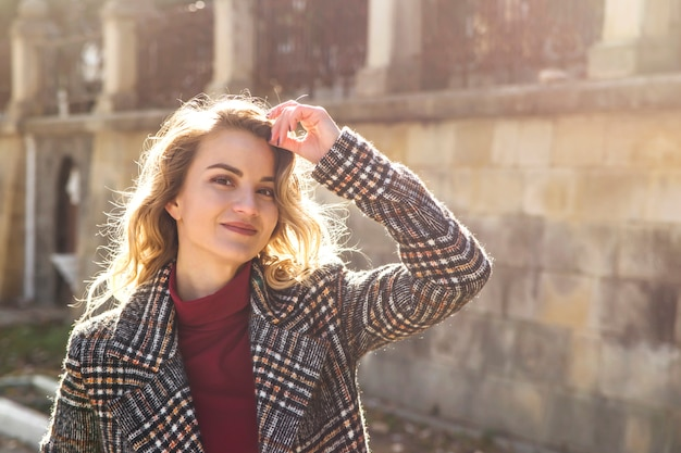 Portrait of a beautiful modern girl with blonde wavy hair in autumn coat in sunlight. Premium Photo