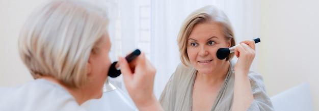 鏡を見て彼女の完璧な肌に触れる肖像画美しい老woman。彼女の顔の肌に触れるブラシで成熟した女性の顔を閉じます。 Premium写真