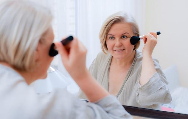 肖像画の鏡を見ている彼女の完璧な肌に触れる美しい老婆。顔の皮膚にブラシで触れる成熟した女性の顔をクローズアップ。 Premium写真