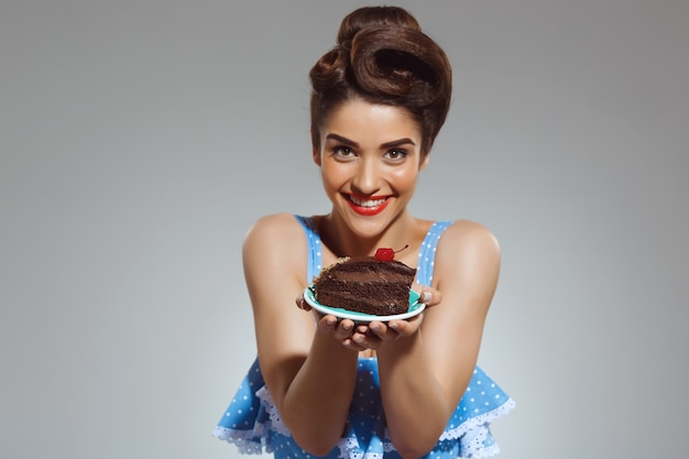 Portrait of beautiful pin-up woman holding cake in hands Free Photo