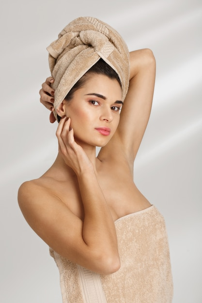Portrait of a beautiful posh young woman after bath standing covered in towel Free Photo