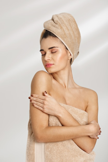 Portrait of a beautiful posh young woman after spa standing covered in towel. Free Photo