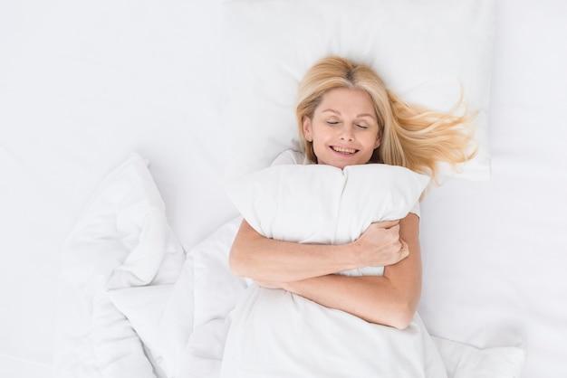 Portrait of beautiful senior woman holding a pillow Free Photo