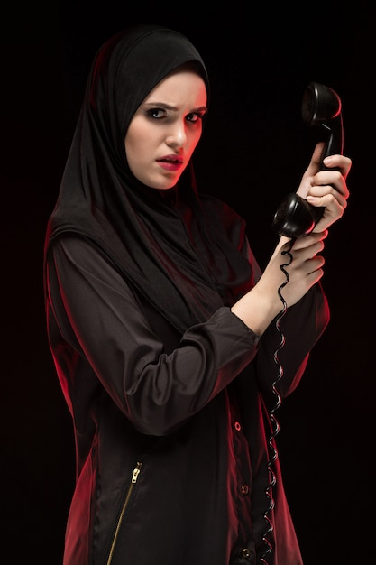 Portrait of beautiful serious scared young muslim woman wearing black hijab calling for help Premium Photo