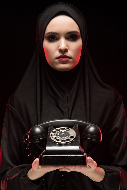 Portrait of beautiful serious scared young muslim woman wearing black hijab offering telephone to call as choice concept Premium Photo