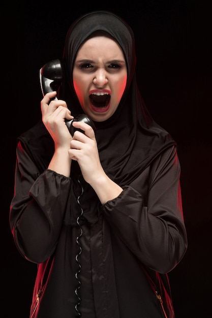 Portrait of beautiful serious scared young muslim woman wearing black hijab screaming calling for help on black Premium Photo