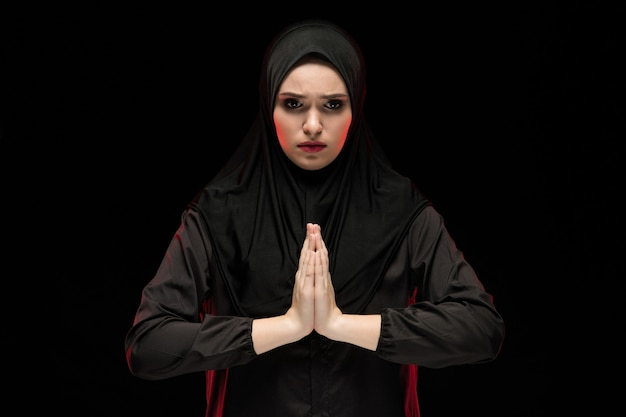 Portrait of beautiful serious young muslim woman wearing black hijab with hands near her face as praying concept on black background Premium Photo