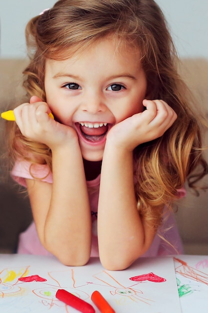 Portrait of a beautiful smiling child of european appearance with curly hair on the background of children's drawings. Premium Photo