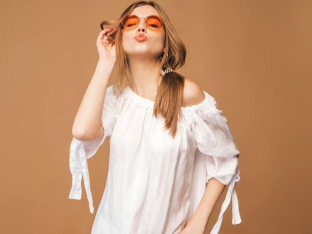 Portrait of beautiful smiling cute model with pink lips. girl in summer white dress. model posing in sunglasses. giving kiss Free Photo