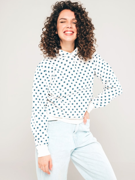 Portrait of beautiful smiling model with afro curls hairstyle dressed in summer hipster clothes.sexy carefree girl posing in studio on gray background.trendy funny and positive woman Free Photo