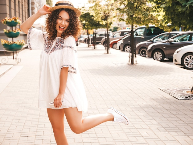 Portrait of beautiful smiling model with afro curls hairstyle dressed in summer hipster white dress. Free Photo