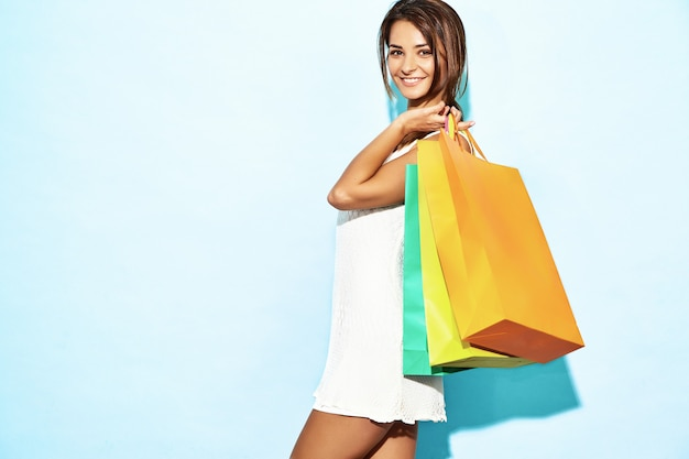 Portrait of beautiful smiling shopaholic woman holding colorful paper bags. brunette woman posing on blue wall after shopping. positive model Free Photo