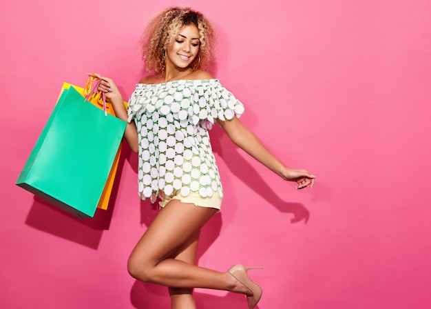 Portrait of beautiful smiling shopaholic woman holding colorful paper bags Free Photo