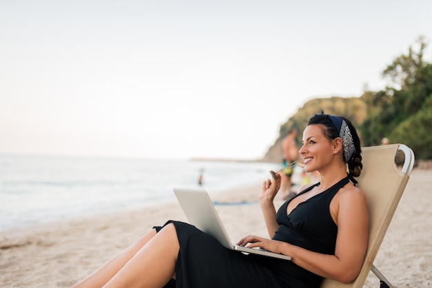 Portrait of a beautiful smiling young woman sitting on the beach with laptop. Premium Photo