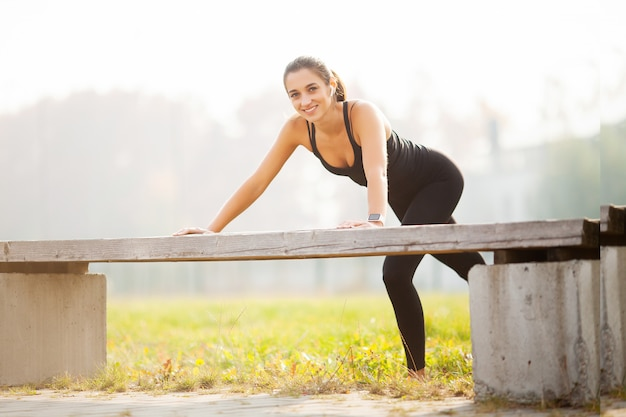 Portrait of beautiful sporty woman 20s in sportswear doing push-ups, and listening to music with bluetooth earbud during workout in green park Premium Photo