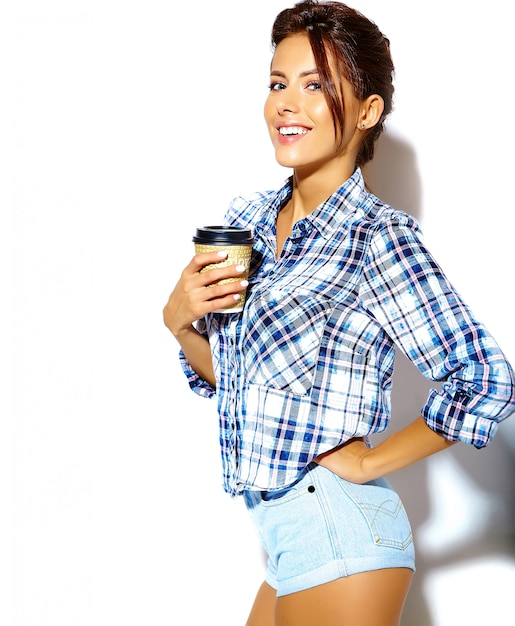 Portrait of beautiful stylish cool  teenage woman in checkered shirt, holding plastic coffee cup Free Photo
