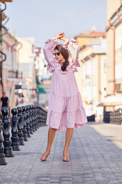 Portrait of beautiful stylish model in pink dress posing with hands up Premium Photo