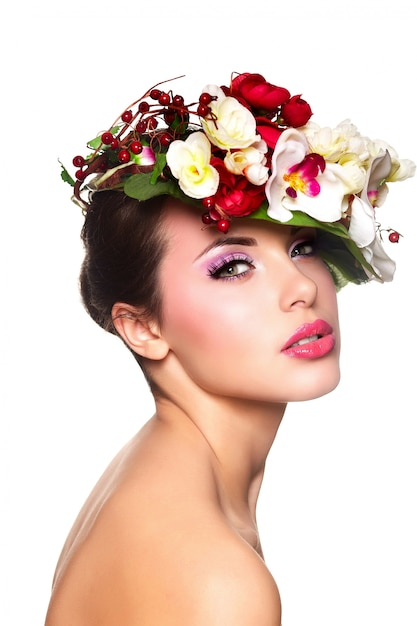 Portrait of beautiful stylish young woman with colorful flowers on head Free Photo