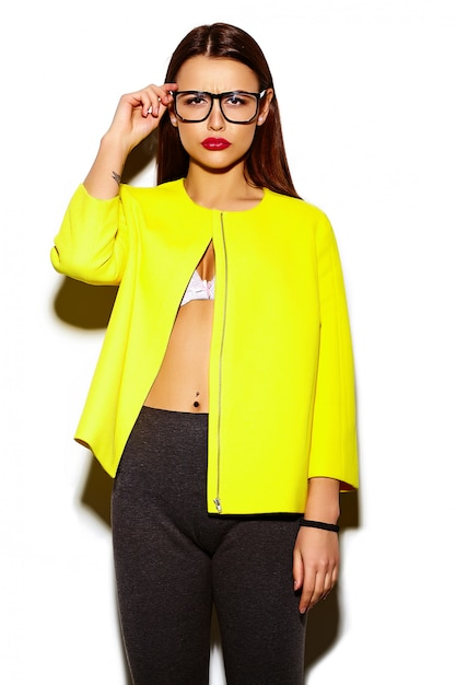 Portrait of beautiful stylish young woman in yellow coat and with glasses Free Photo
