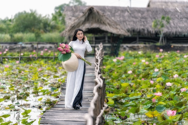 Portrait of beautiful vietnamese woman with traditional vietnam hat holding the pink lotus Premium Photo