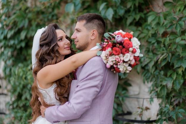 Ritratto di una bella coppia di sposi di fronte a un muro coperto di foglie verdi Foto Gratuite