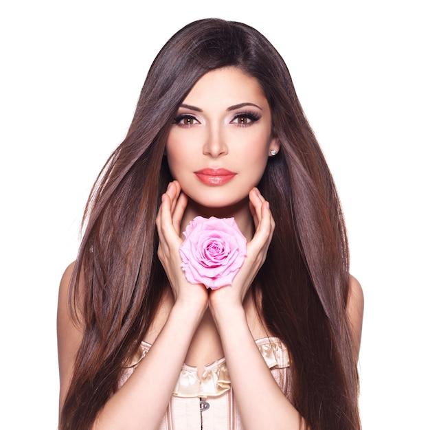 Ritratto di una bella donna graziosa bianca con lunghi capelli lisci e rosa rosa sul viso. Foto Gratuite