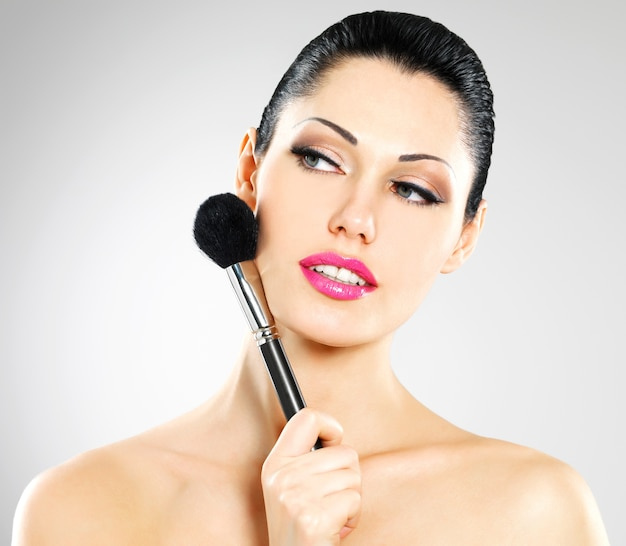 Portrait of  beautiful woman applying blusher on face using cosmetic brush Free Photo