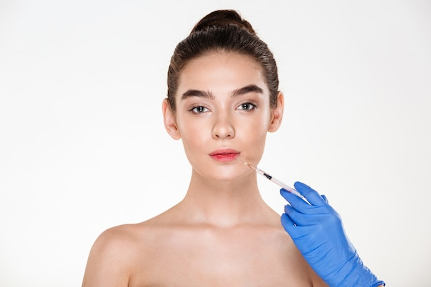 Portrait of beautiful woman getting injection in her lips with botox having plastic surgery in clinic Free Photo