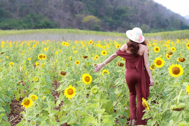 Portrait of beautiful woman having a happy time and enjoying among sunflower field in nature Premium Photo