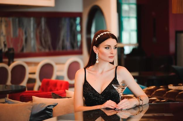 Portrait of beautiful woman holding glass of martini. Premium Photo