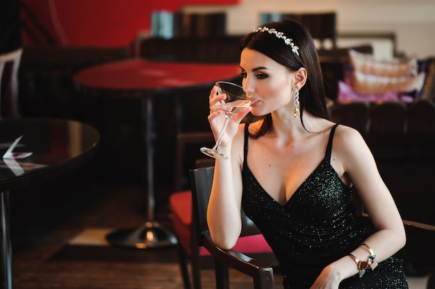 Portrait of beautiful woman holding glass of martini. Premium Photo