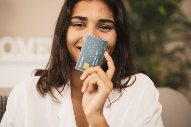 Portrait of a beautiful woman showing a credit card Free Photo
